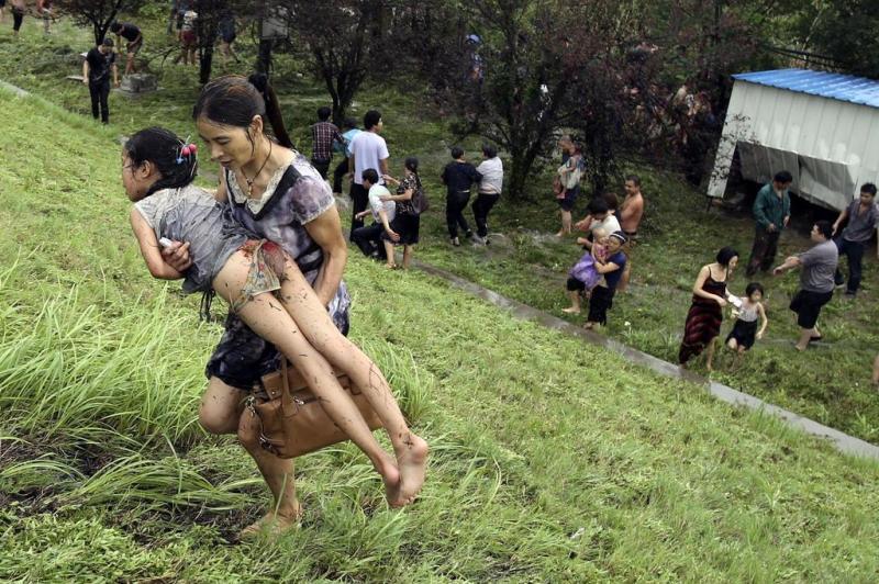 Mulher carrega menina após passagem das ondas gigantes:imagem 6